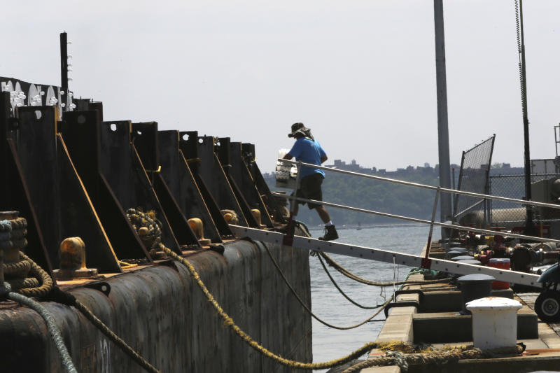 A Pyro Spectaculars by Souza workers loads materials onto a barge docked in the Staten Island borough of New York, Saturday, June 29, 2013. Forty thousand shells are being loaded onto four barges in preparation for the Macy's Fourth of July fireworks display. (AP Photo/Mary Altaffer)