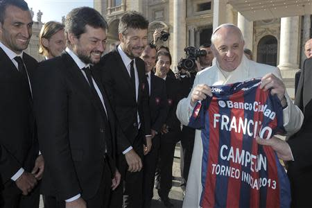 Pope Francis holds a jersey of Argentine soccer team San Lorenzo, given to him as a gift from members of the team, during the Wednesday general audience in St Peter's Square at the Vatican December 18, 2013. REUTERS/Osservatore Romano
