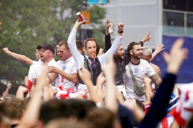An England fan dressed as Gareth Southgate pours beer over his own head