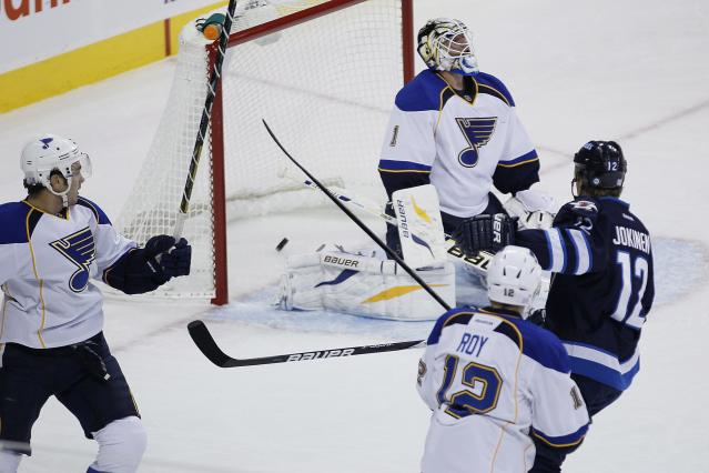 Winnipeg Jets' Olli Jokinen (12) scores on St. Louis Blues goaltender Brian Elliot during the first period of an NHL hockey game, Friday, Oct. 18, 2013 in Winnipeg, Manitoba. (AP Photo/The Canadian Press, John Woods)