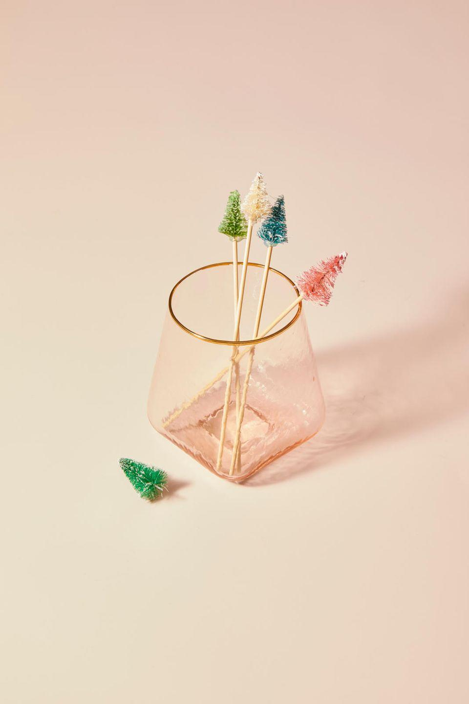 """<p>For cocktails that are extra festive, cut drink skewers down until they're about 3"""" long, then attach a <a href=""""https://www.amazon.com/Haiabei-Christmas-Crafting-Displaying-Decoration/dp/B07JLZ1SPV/?tag=syn-yahoo-20&ascsubtag=%5Bartid%7C10055.g.2996%5Bsrc%7Cyahoo-us"""" rel=""""nofollow noopener"""" target=""""_blank"""" data-ylk=""""slk:mini bottle brush tree"""" class=""""link rapid-noclick-resp"""">mini bottle brush tree</a> to the top with a dot of hot glue.</p><p><strong>RELATED: </strong><a href=""""https://www.goodhousekeeping.com/holidays/christmas-ideas/g29327296/bottle-brush-christmas-tree-online/"""" rel=""""nofollow noopener"""" target=""""_blank"""" data-ylk=""""slk:Where to Buy Bottle Brush Christmas Trees Online"""" class=""""link rapid-noclick-resp"""">Where to Buy Bottle Brush Christmas Trees Online</a></p>"""
