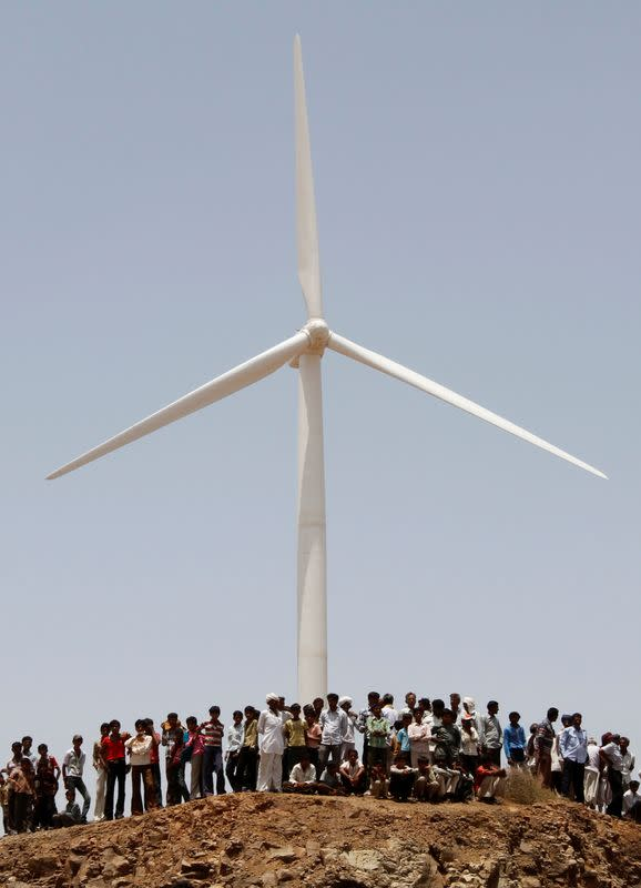 FILE PHOTO: Villagers stand under a power generating windmill turbine during the inauguration ceremony of the new 25 MW ReNew Power wind farm at Kalasar village