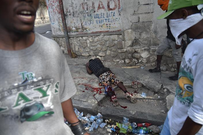 <p>A wounded man lies on a road following clashes with Haitian Police during a protest against the increase in fuel prices, July 7, 2018 in Port-au-Prince. (Photo: Hector Retamal/AFP/Getty Images) </p>
