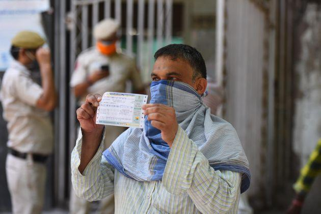 A man holds a railway ticket outside the reservation counter that was reopened following the ease in lockdown restrictions, in New Delhi Railway Station, on May 22, 2020 in New Delhi.