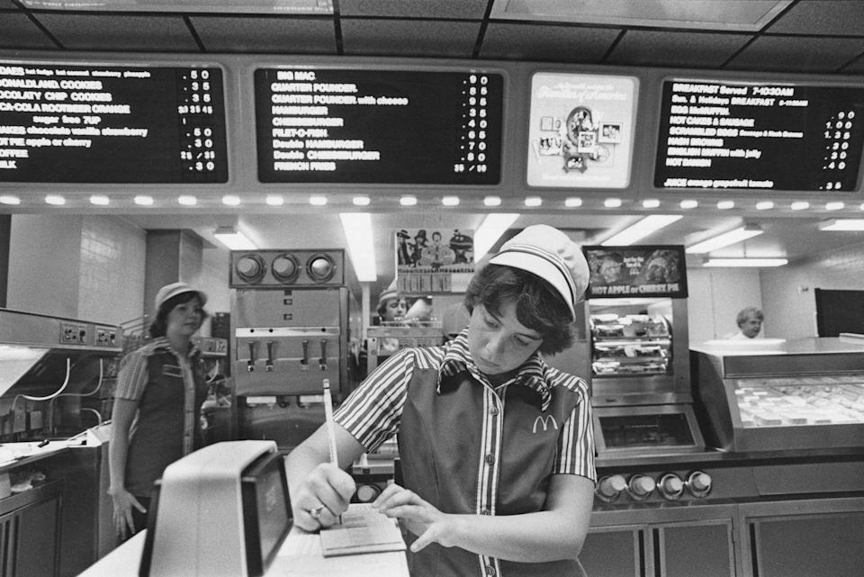 <p>An employee wearing the McDonald's uniform with stripes and a white hat takes down an order in 1978, long before automated technology.</p>