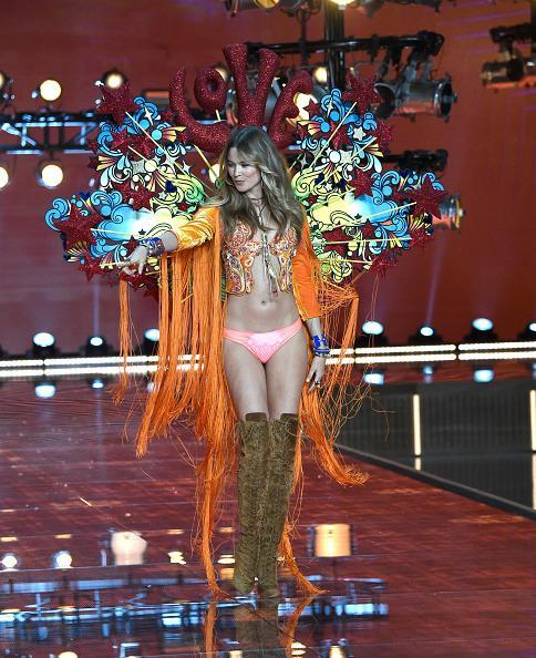 """<p>There's no one more fitting to open the """"Boho Psychedelic"""" section of the show than ultimate hippie babe Behati Prinsloo. The wings read out """"LOVE"""" in big red block letters surrounded by colorful doodles, she wore a cardigan lined with bright orange fringe, and walked the walk in some super trendy suede thigh-high boots. If the Victoria's Secret Fashion Show took place in the swinging sixties, this is totally what it would look like. </p>"""