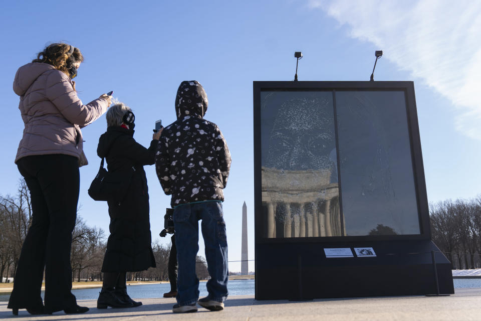 "People photograph the installation ""Vice President Kamala Harris Glass Ceiling Breaker"" at the Lincoln Memorial in Washington, Wednesday, Feb. 4, 2021. Vice President Kamala Harris' barrier-breaking career has been memorialized in a portrait depicting her face emerging from the cracks in a massive sheet of glass. Using a photo of Harris that taken by photographer Celeste Sloman, artist Simon Berger lightly hammered on the slab of laminated glass to create the portrait of Harris. The Washington Monument is seen in the distance and the Lincoln Memorial is reflected. (AP Photo/Carolyn Kaster)"