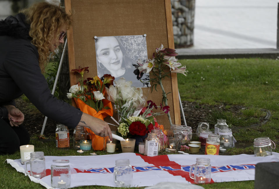 A woman lights candles during a candlelight vigil for murdered British tourist Grace Millane at Cathedral Square in Christchurch, New Zealand, Wednesday, Dec. 12, 2018. (AP Photo/Mark Baker)