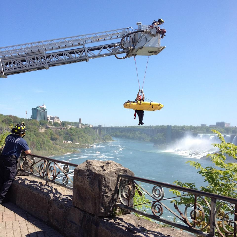 In this photo provided by Jared Fisk, Niagara Falls emergency officials rescue a man who plunged over Niagara Falls and survived in an apparent suicide attempt, Monday, May 21, 2012. The man is only the third person known to have gone over without a safety device and live. A waiting helicopter flew him to Hamilton General Hospital, where a spokeswoman says he has critical but non-life-threatening injuries. (AP Photo/Jared Fisk)