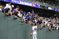 National League coach Dino Ebel, of the Los Angeles Dodgers, gives a ball to a fan prior to the MLB All-Star baseball game, Tuesday, July 13, 2021, in Denver. (AP Photo/Jack Dempsey)