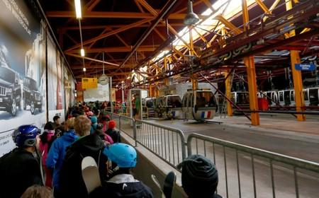 FILE PHOTO: Tourists queue in a station of the Titlisbahnen cablecar in Engelberg