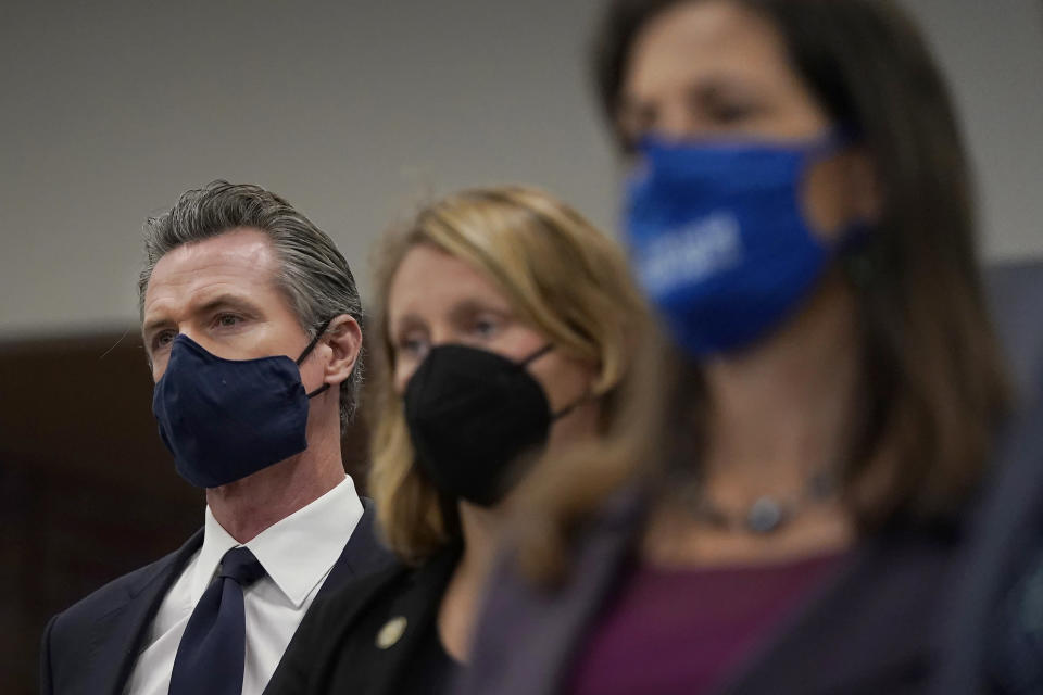 Gov. Gavin Newsom, from left, Assemblywoman Buffy Wicks, D-Oakland, and Oakland Mayor Libby Schaaf listen to spekers at a news conference in Oakland, Calif., Monday, July 26, 2021. California will require state employees and all health care workers to show proof of COVID-19 vaccination or get tested weekly. Officials are tightening restrictions in an effort to slow rising coronavirus infections in the nation's most populous state, mostly among the unvaccinated. (AP Photo/Jeff Chiu)