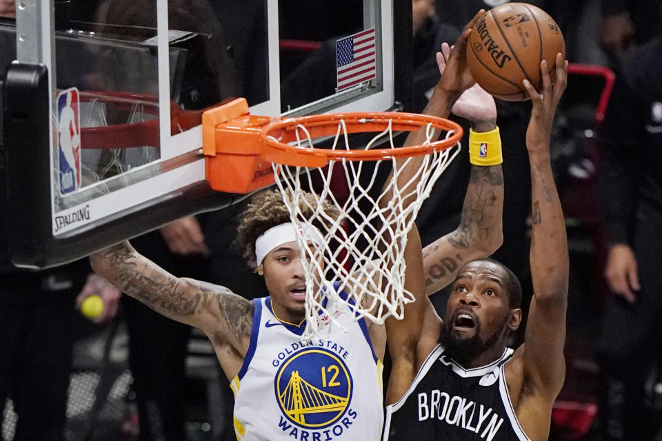 Brooklyn Nets forward Kevin Durant (7) shoots as Golden State Warriors forward Kelly Oubre Jr., (12) defends during the first quarter of an opening night NBA basketball game, Tuesday, Dec. 22, 2020, in New York. (AP Photo/Kathy Willens)