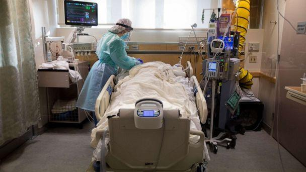 PHOTO: Registered Nurse Joan Pung, works in a COVID-19 patient's room inside the ICU at Providence St. Jude Medical Center on Dec. 25, 2020, in Fullerton, Calif. (Francine Orr/Los Angeles Times via Getty Images)