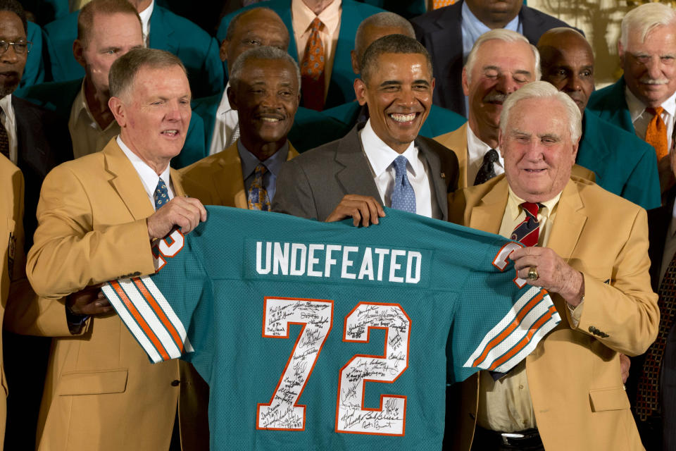 Former Miami Dolphins football quarterback Bob Griese, left, President Barack Obama and 1972 Dolphins Coach Don Shula, right, hold a signed jersey in the East Room of the White House in Washington, Tuesday, Aug. 20, 2013, during a ceremony honoring the Super Bowl VII football Champion Miami Dolphins. The 1972 Miami Dolphins remain the only undefeated team in NFL history. Form left are, Griese, wide receiver Paul Warfield, the president, running back Larry Csonka and Shula. (AP Photo/Jacquelyn Martin)