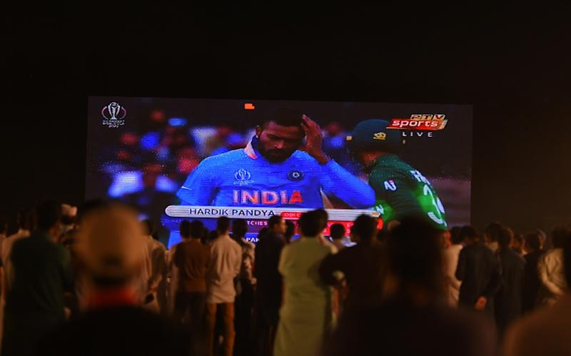 Pakistani fans gather in a park in Islamabad to watch the match against India on a big screen (AFP Photo/FAROOQ NAEEM)