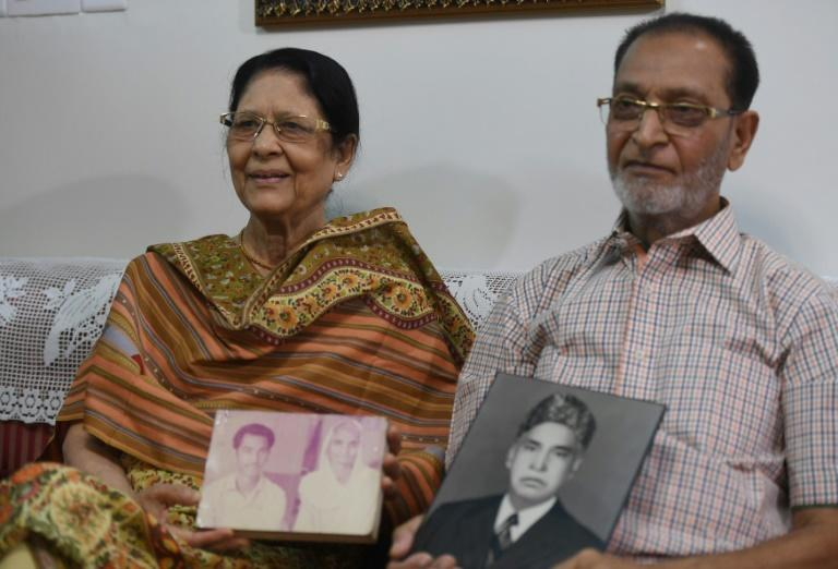 Nisar Akhtar, 76, and his wife Naushaba Siddiqui pose with pre-Partition photos during an interview with AFP in Karachi