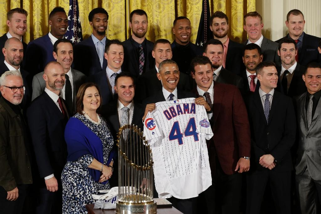 US President Barack Obama poses with a jersey as he welcomes the World Champion Chicago Cubs baseball team to the White House on January 16, 2017 (AFP Photo/YURI GRIPAS)