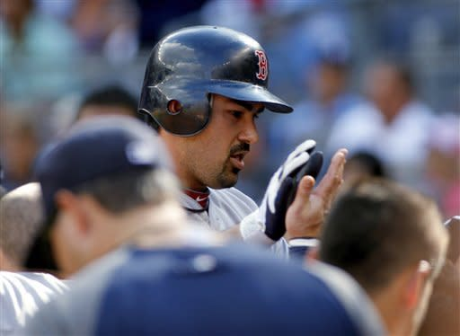 Boston Red Sox's Adrian Gonzalez is congratulated as he returns to the dugout after hitting a two-run home run off of New York Yankees' David Phelps in the first inning of a baseball game Saturday, Aug. 18, 2012, at Yankee Stadium in New York. (AP Photo/John Dunn)