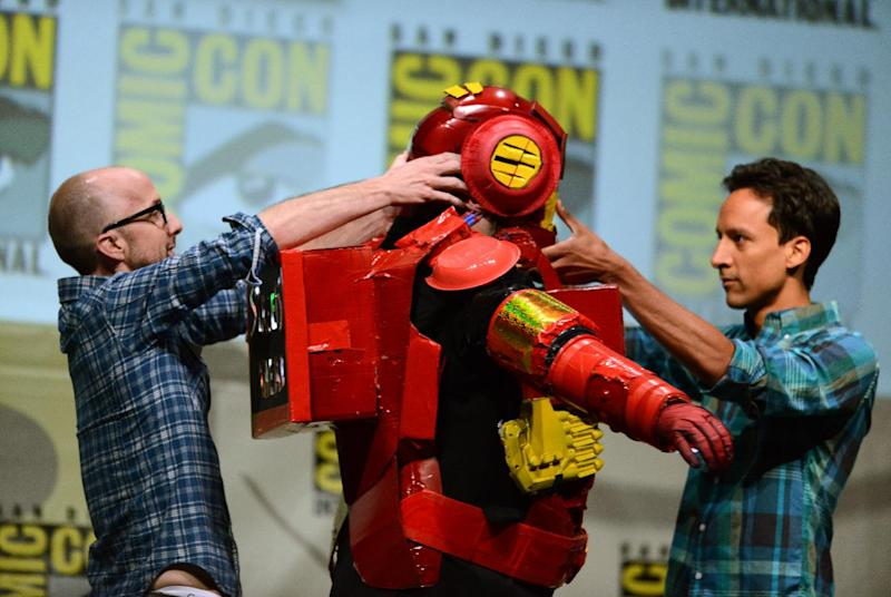 """Dan Harmon, center, is helped out of a costume by Jim Rash, left, and Danny Pudi during the """"Community"""" panel on Day 5 of Comic-Con International on Sunday, July 21, 2013, in San Diego. (Photo by Jordan Strauss/Invision/AP)"""