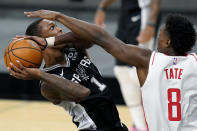 San Antonio Spurs guard Lonnie Walker IV (1) drives to the basket against Houston Rockets forward Jae'Sean Tate (8) during the first half of an NBA basketball game in San Antonio, Thursday, Jan. 14, 2021. (AP Photo/Eric Gay)