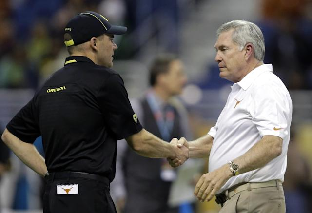 Oregon coach Mark Helfrich, left, shakes hands with Texas coach Mack Brown, right, before the Valero Alamo Bowl NCAA college football game, Monday, Dec. 30, 2013, in San Antonio. (AP Photo/Eric Gay)