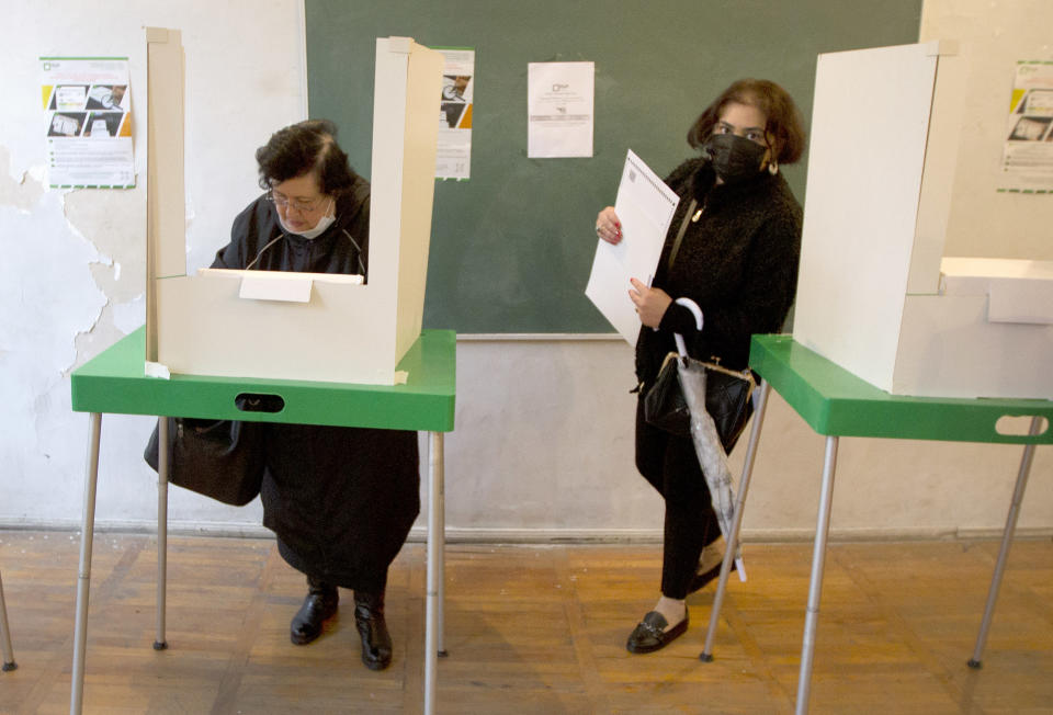 Women vote at a polling station during national municipal elections in Tbilisi, Georgia, Saturday, Oct. 2, 2021. Georgians are voting in municipal elections across the country that are seen as a strength test for the ruling party and that opposition parties hope could lead to early national elections. (AP Photo/Shakh Aivazov)