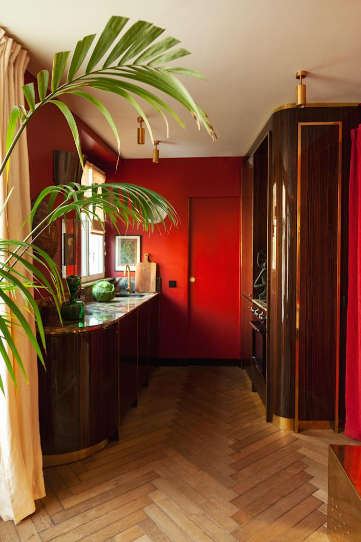 In the kitchen, the red color and lacquered wood give the feeling of being on a train or in a boat. The wall lighting fixture was designed by Hugo Toro and the curtains are by Silva Créations.