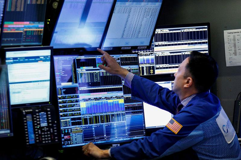A trader works inside a stall on the floor of the New York Stock Exchange (NYSE) in New York, U.S., October 3, 2017. REUTERS/Brendan McDermid/Files