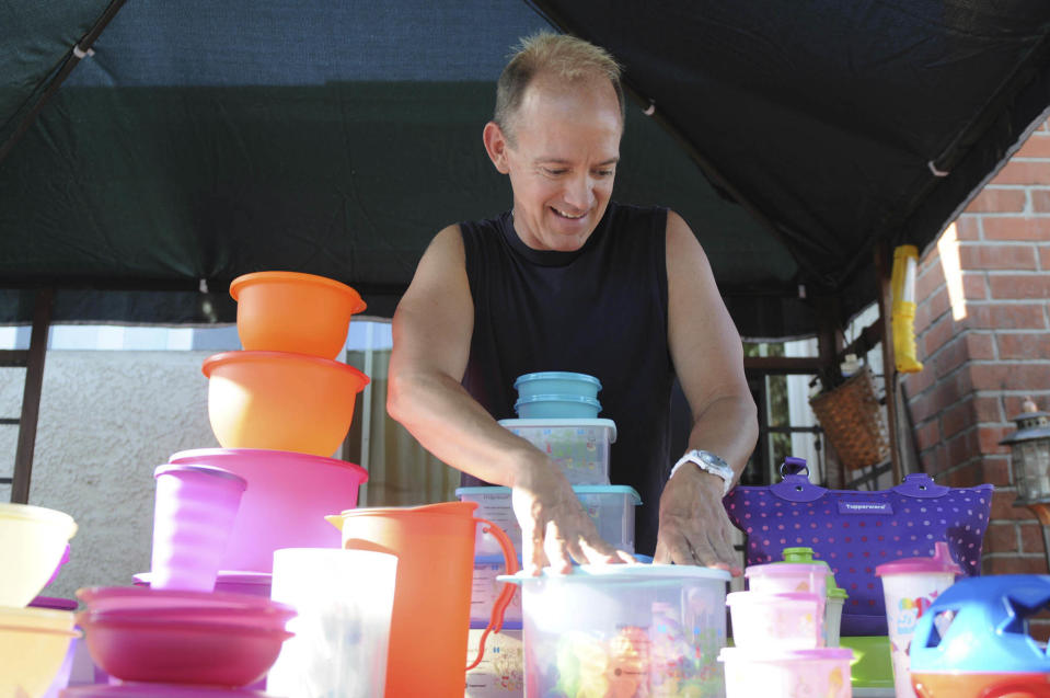 Kevin Farrell stacks some of his Tupperware products on a table while preparing for a Tupperware party in Bellflower, Calif. (AP Photo/Garrett Cheen)