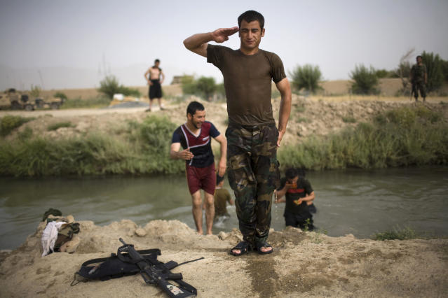 <p>An Afghan army soldier poses after swimming in a canal near the joint Afghan-U.S. base COP Nolen, in the volatile Arghandab Valley, Kandahar, Afghanistan, July 22, 2010. (Photo: Rodrigo Abd/AP) </p>