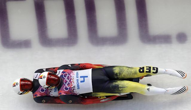 The doubles team of Tobias Wendl and Tobias Arlt from Germany speeds down the track in their first run during the men's doubles luge at the 2014 Winter Olympics, Wednesday, Feb. 12, 2014, in Krasnaya Polyana, Russia. (AP Photo/Michael Sohn)