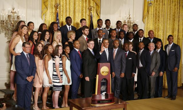 U.S. President Barack Obama poses with team members of the 2014 NCAA champion UConn Huskies men's and women's basketball teams after receiving team jerseys while in the East Room of the White House in Washington, June 9, 2014. REUTERS/Larry Downing (UNITED STATES - Tags: POLITICS SPORT BASKETBALL)