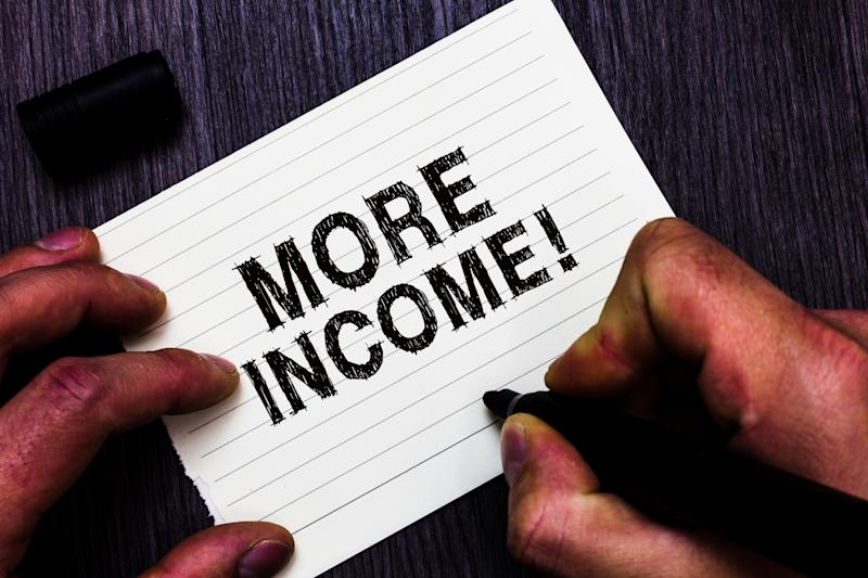 We see two hands writing the words more income on an index card.