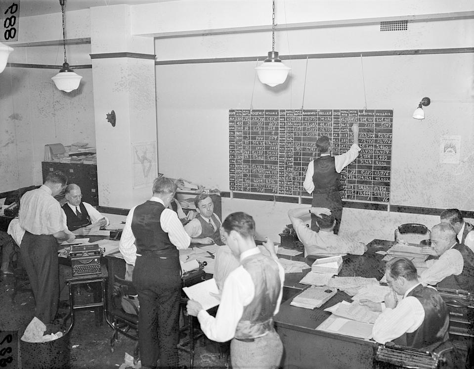 Associate Press journalists in the Washington bureau tabulate election returns, Nov. 5, 1940, keeping the score on both electoral and popular votes for the nation. The staff handled returns which flooded in over an 85,000-mile wire network. Standing is Brian Bell, left, chief of bureau for Washington, D.C. seated with back to camera is William L. Beale, Washington news editor. (AP Photo)
