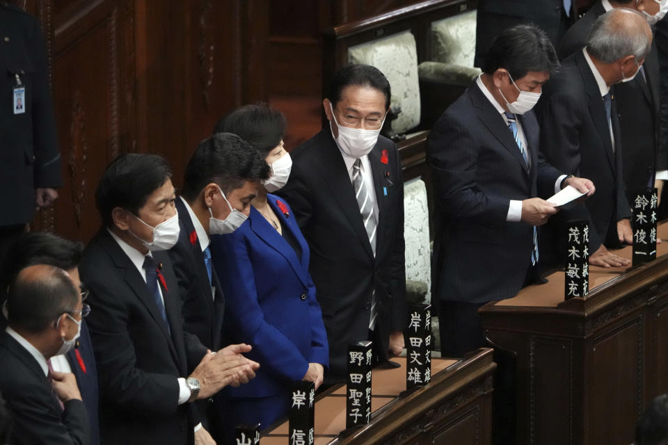 Japanese Prime Minister Fumio Kishida, center, and other lawmakers speak after dissolving the lower house, at an extraordinary Diet session at the lower house of parliament Thursday, Oct. 14, 2021, in Tokyo. (AP Photo/Eugene Hoshiko)