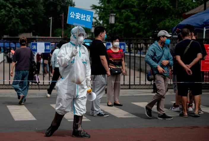 A medical professional in full protective gear holds a sign to help people who are close by or who have visited the Xinfadi Market, a wholesale food market where a new cluster of coronavirus COVID-19 has appeared when they arrive for testing on June 17 in Beijing. 2020.