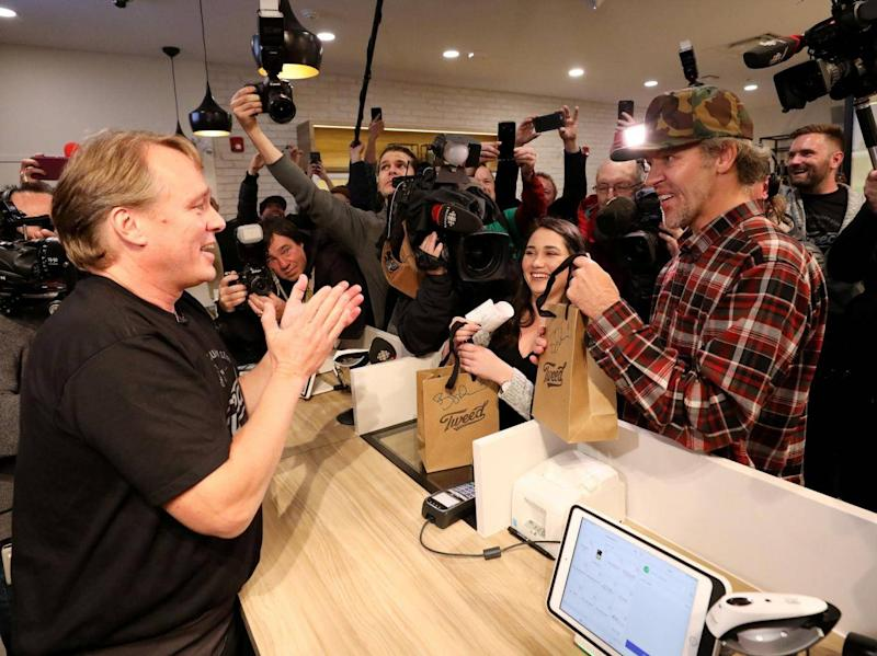 Canopy Growth CEO Bruce Linton hands Ian Power and Nikki Rose the first legal recreational marijuana purchases after midnight at a store in St John's, Newfoundland and Labrador, Canada (REUTERS)
