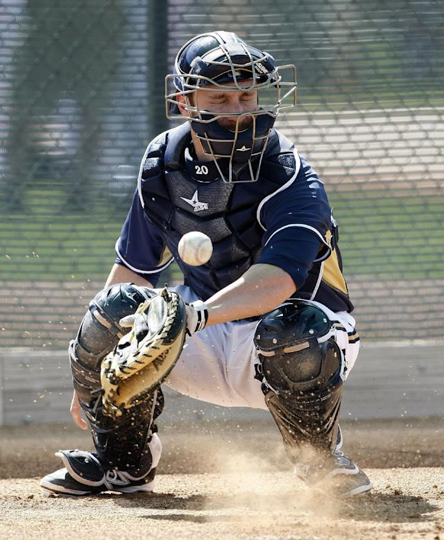Milwaukee Brewers catcher Jonathan Lucroy (20) blocks a ball in the dirt during a spring training baseball practice, Sunday, Feb. 22, 2014, in Phoenix. (AP Photo/Rick Scuteri)