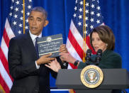 FILE - In this Jan. 28, 2016 file photo, President Barack Obama, left, is presented a copy of the Iran Nuclear Agreement Legislation by House Minority Leader Nancy Pelosi, in Baltimore, Md. President-elect Joe Biden has pledged to potentially return American to Iran's 2015 nuclear deal with world powers, which saw Tehran limit its enrichment of uranium in exchange for the lifting of economic sanctions. Trump unilaterally pulled out of the deal in 2018. (AP Photo/Pablo Martinez Monsivais, File)