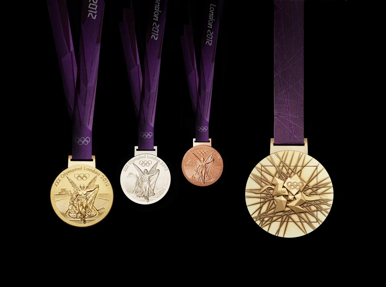 A handout image obtained from the London 2012 organising committee (LOCOG) on July 27, 2011 shows the London 2012 Olympic medals designed by British artist David Watkins. The Olympic medals' circular form is a metaphor for the world. The front of the medal always depicts the same imagery at the summer Games, the Greek Goddess of Victory, Nike, stepping out of the depiction of the Parthenon to arrive in the host city. The design for the reverse of the London 2012 Olympic medals contains five main symbolic elements: the dished background suggests a bowl similar to the design of an amphitheatre, the core emblem is an architectural expression, a metaphor for the modern City, the grid brings both a pulling together and sense of outreach on the design - an image of radiating energy that represents the athletes' achievements and effort, the River Thames is a symbol for London and the square is the final balancing motif of the design, opposing the overall circularity of the design and emphasising its focus on the centre and reinforcing the sense of 'place' as in a map inset. AFP PHOTO / LOCOG/ HO  ATTENTION - EMBARGO, RELEASABLE Wednesday July 27, 2011 at 1830 GMT - THIS RESTRICTION APPLIES TO ALL MEDIA INCLUDING WEBSITES   ---- EDITORS NOTE ---- RESTRICTED TO EDITORIAL USE - MANDATORY CREDIT *AFP PHOTO / LOCOG/ HO* - NO MARKETING NO ADVERTISING CAMPAIGNS - DISTRIBUTED AS A SERVICE TO CLIENTS (Photo credit should read HO/AFP/Getty Images)