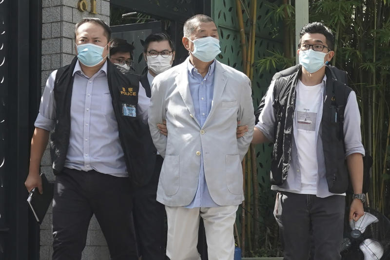 Hong Kong media tycoon Jimmy Lai, center, who founded local newspaper Apple Daily, is arrested by police officers at his home in Hong Kong, Monday, Aug. 10, 2020. Hong Kong police arrested Lai and raided the publisher's headquarters Monday in the highest-profile use yet of the new national security law Beijing imposed on the city after protests last year. (AP Photo)