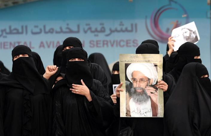 Saudi Shiite women hold placards bearing portraits of prominent Shiite Muslim cleric Nimr al-Nimr during a protest in the eastern coastal city of Qatif against his execution by Saudi authorities, on January 2, 2016 (AFP Photo/)