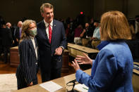 Republican gubernatorial candidate Glenn Youngkin, center, and his wife, Suzanne, left, greet debate moderator Susan Page, right after a debate with Democrat Terry McAuliffe at the Appalachian School of Law in Grundy, Va., Thursday, Sept. 16, 2021. (AP Photo/Steve Helber)
