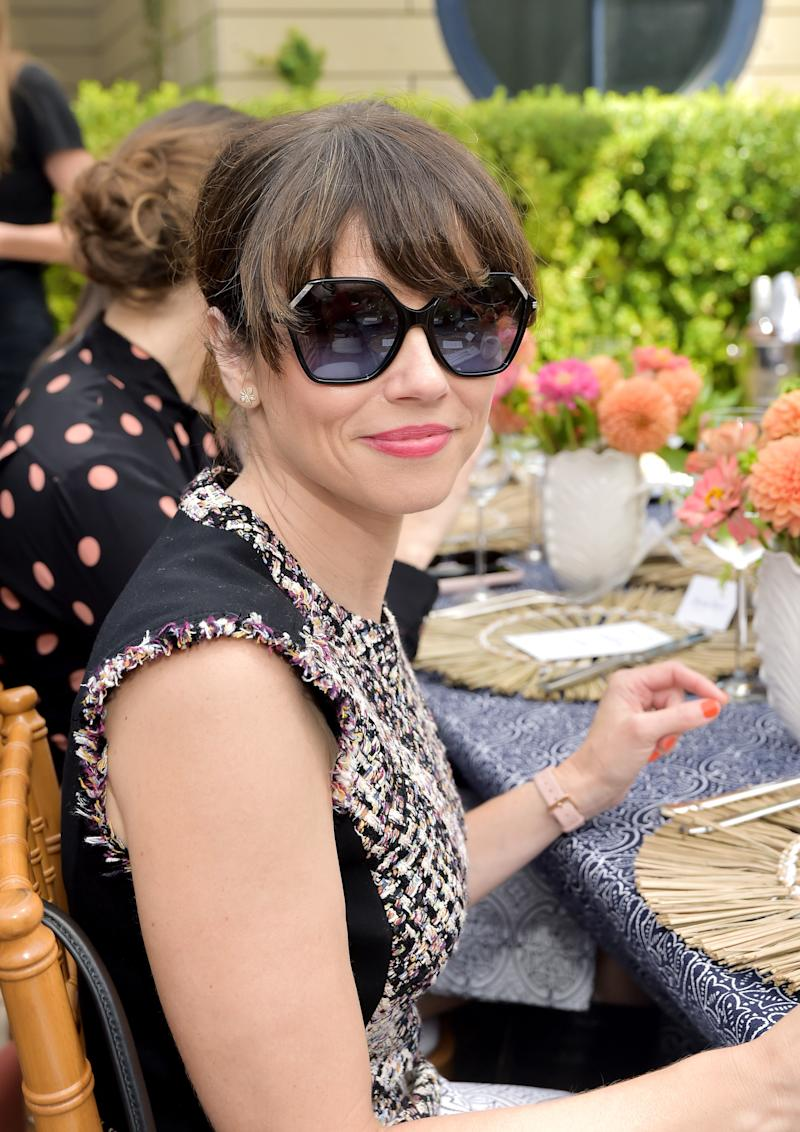 Linda Cardellini is wearing the Tweed Pencil Dress, Penelope Slingback Pump, Lee Radziwill Small Bag, Gigi Watch, and Oversized Inlay Sunglasses
