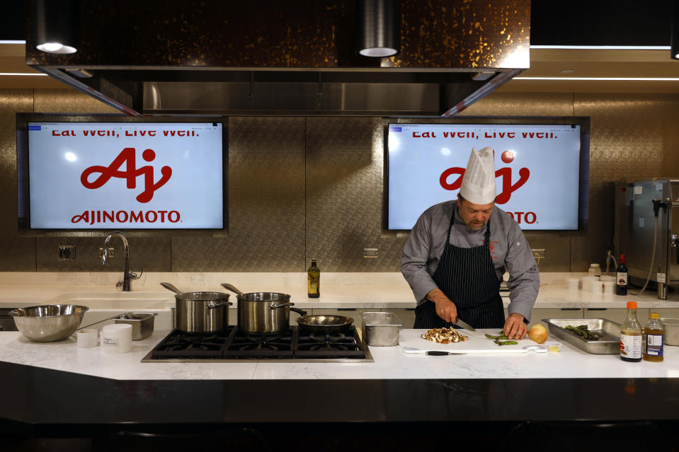 Christopher Koetke, head chef of Ajinomoto, a global food and pharmaceutical company, prepares a meal at the office customer engagement center in Itasca, Ill., Monday, June 7, 2021. In May, Ajinomoto's employees returned to in-person work in a space designed for a post-COVID world. Hallways are wider. Glass panels separate cubicles. The culinary center is wired for virtual presentations. And a cleaning crew comes through twice a day, leaving Post-it notes to show what's been disinfected. (AP Photo/Shafkat Anowar)