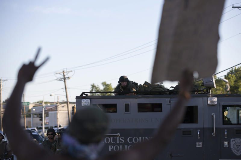 A police officer aims his weapon at a demonstrator in Ferguson, Aug. 13, 2014.  (Mario Anzuoni / Reuters)