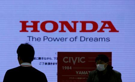 Men are silhouetted against a logo of Honda Motor at the company's showroom in Tokyo