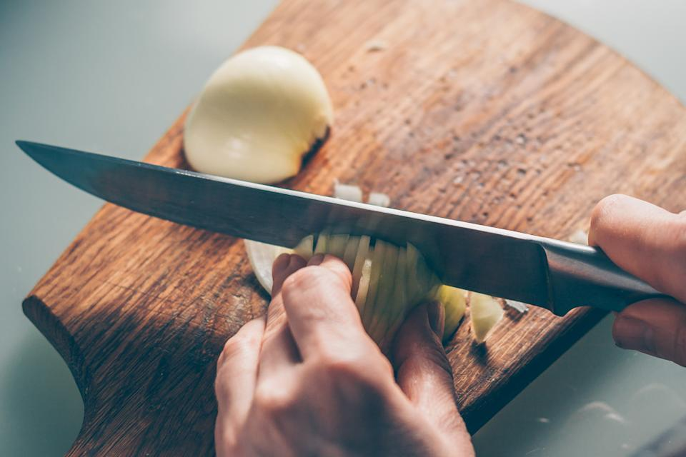 The cook cuts the onion on a cutting board