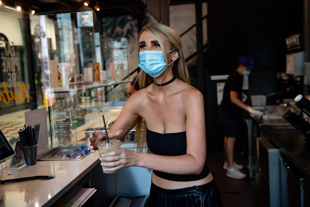 A bartender in Birmingham serves a drink while wearing a mask. (Getty Images)